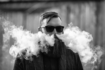 Vape man. Outdoor portrait of a young brutal white guy with large beard and in sunglasses letting puffs out of steam from an electronic cigarette opposite the old wooden fence. Black and white.