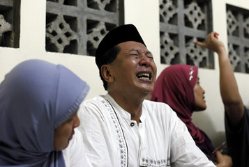 The father of a train crash victim reacts after receiving confirmation of his son's death at a hospital morgue in Pemalang