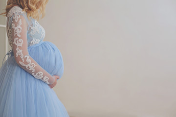 Close up photo Charming tummy of pregnant woman in a blue lace and chiffon fluffy dress touching her belly with hands indoors. Maternity sessions