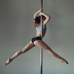 Obraz Young woman exercise pole dance gray background - fototapety do salonu