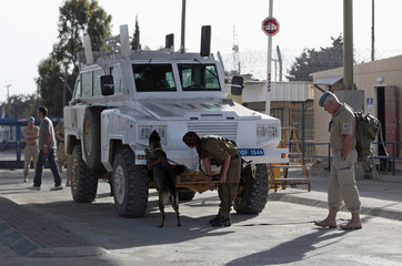 U.N. peacekeeping soldier from Austria watches as Israeli soldier and sniffer dog examine vehicle entering Israeli side of Quneitra border crossing between Israel and Syria, on Israeli-occupied Golan Heigh