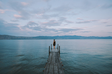 Woman standing on a pier by the lake