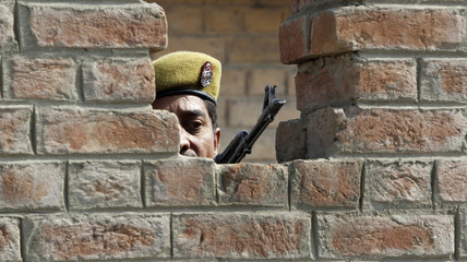 An Indian policeman keeps guard from a bunker after a grenade blast in a market in Srinagar