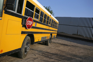 A school bus is parked in front of the border fence at the United States-Mexico border outside Brownsville