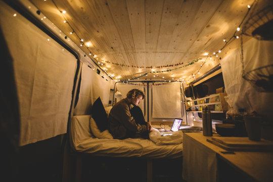 Woman in camper van checking laptop