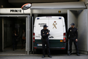 Spanish police stand guard outside the High Court as a van prepares to take former PP regional deputy president Granados to prison in Madrid