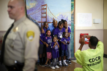 Donte and his wife Candy take a family photo with their children in front of a backdrop of the Golden Gate Bridge at San Quentin state prison