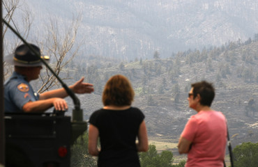 A State Trooper talks to women with a burned area of the High Park Fire in the background near Fort Collins