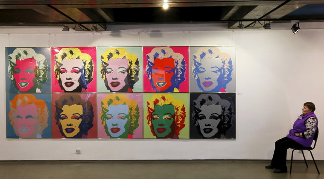 """A woman sits near the """"Marilyn"""" print by Warhol before opening of the """"Pop Art Forum"""" exhibition in Krasnoyarsk"""
