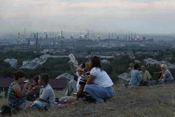 Local residents meet during sunset, with the Metallurgical Plant, or Magnitogorsk Iron and Steel Works, seen in the background, in the Southern Urals city of Magnitogorsk