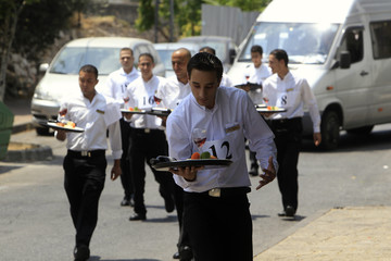 Waiters carry trays as they compete in a race in Jerusalem