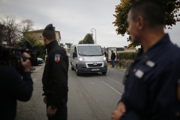 Gendarmes secure the road as hearses transport the remains of victims the day after a fatal crash between a coach and a truck on a country road in Puisseguin