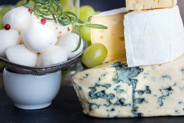 Different types of cheese - brie, camembert, mozarella, blue, roquefrot - with vine, spice peppercorns  on wooden table. Top view. Closeup. Copy space. Selective focus.