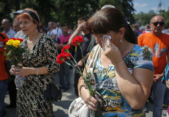 A woman cries during a memorial service for victims of fighting in eastern Ukraine