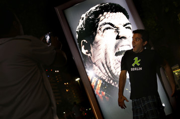 People use their mobile devices to take pictures of an advertising placard showing Uruguay's striker Luis Suarez flashing his teeth at Copacabana beach in Rio de Janeiro