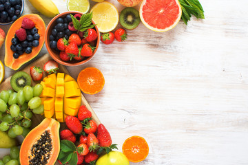 Wall Mural - Colorful fruits on the white wooden table, strawberries, blueberries, mango, orange, grapefruit, banana, apple, grapes, kiwis, copy space for text on the side, selective focus