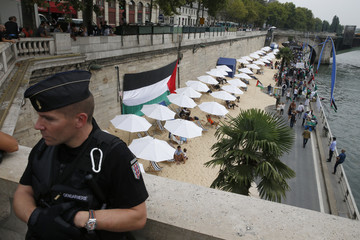 """A French gendarme secures a bridge as a Palestinian flag hangs in protest from a wall behind beach umbrellas placed along the artificial beach along the """"Paris Plages"""" event, in Paris"""