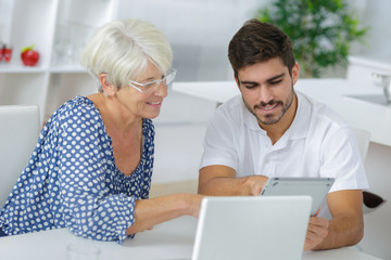 Young man and elderly lady looking at tablet screen