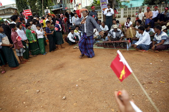 A man dances to traditional music while waiting for Myanmar pro-democracy leader Aung San Suu Kyi's arrival to give a speech on voter education at the Hsiseng township in Shan state