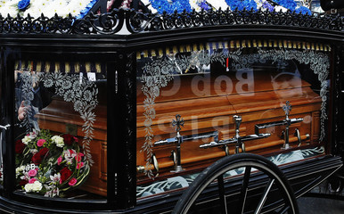 A picture of Bob Crow is reflected on his coffin as it arrives by horse and carriage at the City of London Cemetery and Crematorium in east London