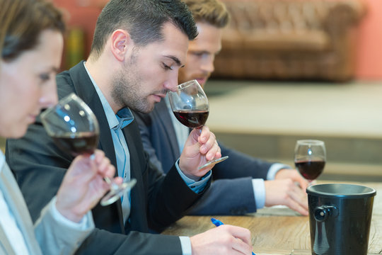three people smelling and evaluating red wine in wineglasses