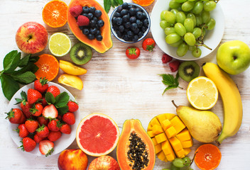 Rainbow color fruits arranged in a circle, strawberries, blueberries, mango, orange, grapefruit, banana, apple, grapes, kiwis on the white background, copy space for text, selective focus