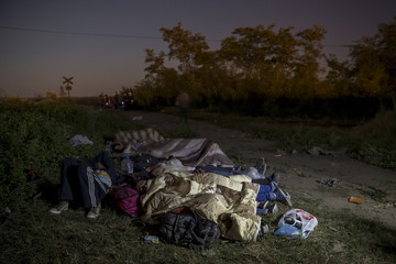 Migrants, hoping to cross into Hungary, sleep on a field outside the village of Horgos in Serbia, towards the border it shares with Hungary