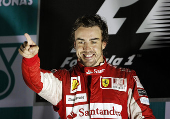 Ferrari Formula One driver Alonso of Spain points as he celebrates on the podium after winning the South Korean F1 Grand Prix at the Korea International Circuit in Yeongam