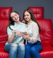 Two girlfriends secretive on red leather couch
