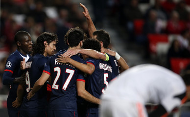 Paris St Germain's players celebrate a goal against Benfica scored by Cavani during their Champions League soccer match in Lisbon