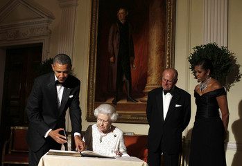U.S. President Barack Obama (L) flips to the page where Queen Elizabeth signs the guest book in London