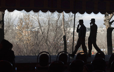 Afghan security personnel keep watch during a ceremony to honour women in conjunction with International Women's day in Kabul