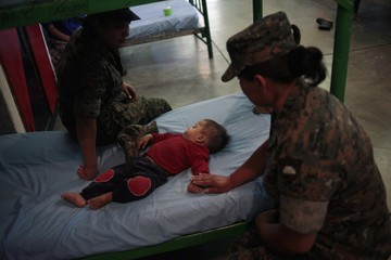 Soldiers look over a baby evacuated from Sinlaj village in a bedroom at the Mariscal Gregorio Solares military base in Huehuetenango