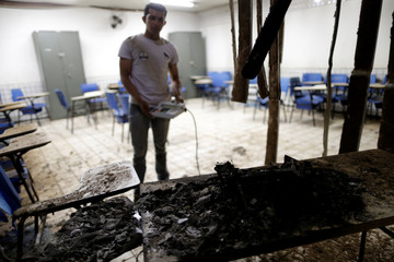 A man looks at a destroyed electronic voting machine after a fire at a polling station during municipal elections in Sao Luis