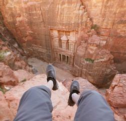 Petra. Traveler sitting above the Treasury. Petra, Jordan.