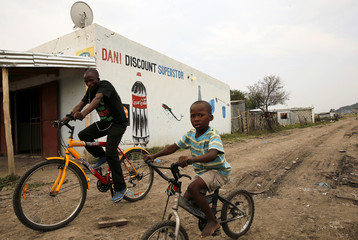 Man and his son cycle past a shop in Nkaneng, Marikana's informal settlement, in Rustenburg