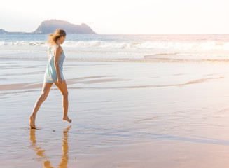 Girl at the seashore runs at sunrise