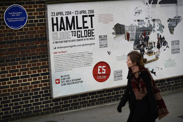 A woman walks by The Globe theatre in London