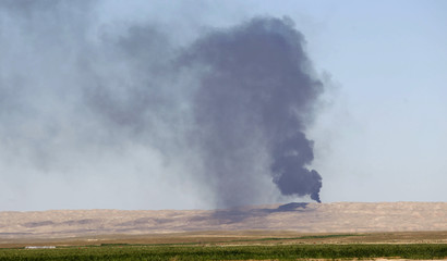 Smoke rises from the Ajil oil field in Al Hadidiya