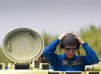 Space shuttle Endeavour STS-134 ESA astronaut Roberto Vittori puts on a helmet before driving an M-113 armored personnel carrier during the terminal countdown demonstration test at the Kennedy Space Center