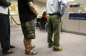 Voters wait in line to cast ballots during in-person absentee voting at the Fairfax County Governmental Center in Fairfax, Virginia