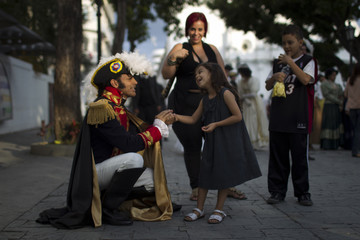 Jesus Abreu (L), representing the South American independence leader Simon Bolivar for a play in the street, talks to a girl in Caracas