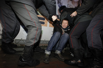 """Russian police remove an activist from the """"Another Russia"""" opposition movement during a meeting to demand the boycott of forthcoming elections in Moscow"""