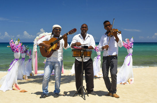 Fiddler, guitarist and drummer in white shirt and grey hat are playing musical instruments on the beach