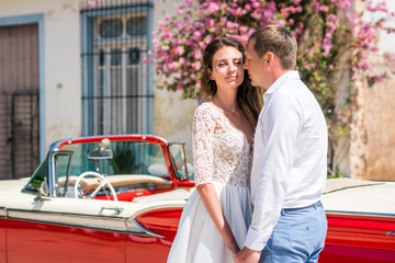 Beautiful couple bride in white wedding dress and groom stand near red retro car cabriolet on the central street in Cuba