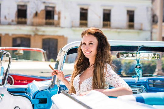 Beautiful young bride in white wedding dress is sitting in blue retro car cabriolet with cigar in her arm