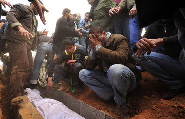 Mournerreact next to grave of a rebel killed by forces loyal to Libyan leader Muammar Gaddafi in Ajdabiyah, during his funeral in Benghazi