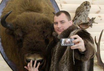 """A man wearing a raccoon jacket, poses for a photo with a stuffed bison during the international exhibition """"Hunting and fishing. Recreation. Spring 2013"""" in Minsk"""