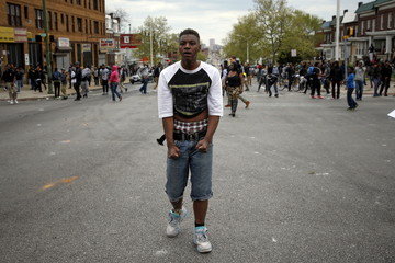 A demonstrator stands on the street after throwing rocks at the Baltimore police during clashes in Baltimore
