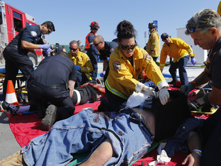 """Emergency personnel attend to """"victims"""" at a triage location back on land during a mock rescue simulating a boating accident in waters off the coast of San Diego, California"""
